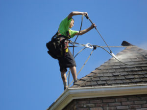 Man cleaning roof tiles atop of a residential building roof.