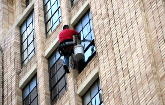 Man cleaning windows of commercial building